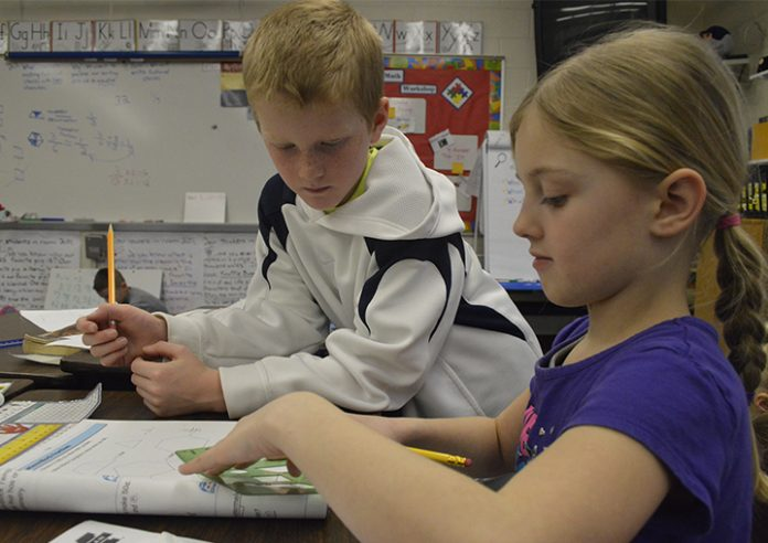 Eli Howland, left, helps Brooke Derosia do an exercise using geometric shapes