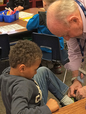 Grandpa Dale stops to help first-grader Cameron Robydek tie his shoe