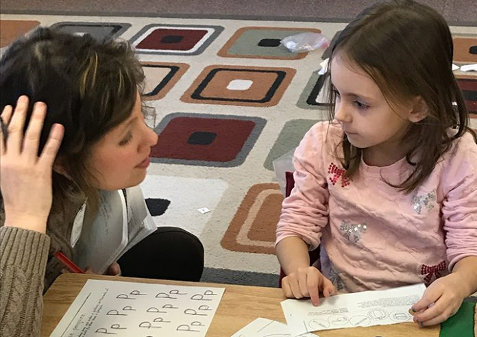 Kent ISD early literacy coach Katie Momber works with a Godfrey-Lee student (Photo courtesy of Kyle Mayer)