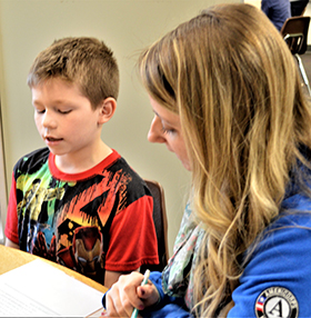 Second-grader Alex Rivera gets a chance to read with Sarah York