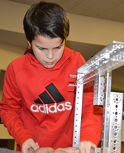 Sixth-grader Cole French checks a connection during early stages of making a team robot