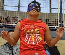 Masked conductor Eyvin Miranda leads from the bleachers