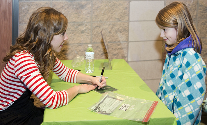 Emily Arrow autographs a card for Caleigh Jones, a second-grader at North Oakview