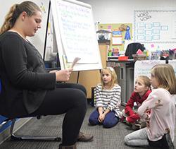 Freshman Mackayla Korreck reads to second-graders Finley Terpstra, Rosie Feldpausch and Josie Pell