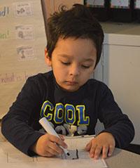 Kindergartner Emiliano Castro, an ELL student, practices spelling
