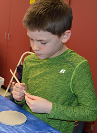 Second-grader Noah Leija envisions a pattern to carve into the wet clay