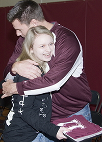 "Genny Swan, a ""Be an 11"" winner, is hugged by a school mentor"