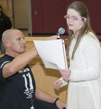 Owen Retan's sister, Gracie, reads a letter praising her brother while event organizer Michael Lapciuk holds a microphone