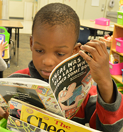 Marquis Morgan chooses a book from a bin in his classroom