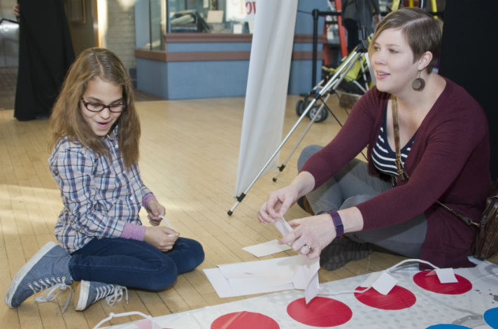 Olivia Clayton, a fourth-grader at Coit Creative Arts Academy, and her mom, Abby, enjoy the challenge of polka dots. Their task was to create a structure that touches as many dots as possible. They could use five each of paper, index cards, mailing labels, pipe cleaners and paper clips. Olivia just realized that she started to meet the challenge