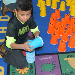 Daniel Montes and other children play a memory game using cups