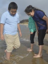 Bravely dipping their feet into the cold water are, left, Alan Ramirez-Becerra and Naudia Radilla-Diego