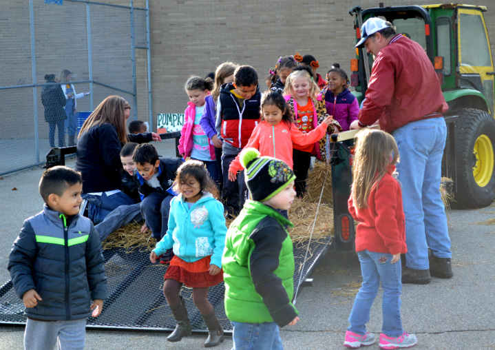 Students climb off the hayride after a tour of the playground