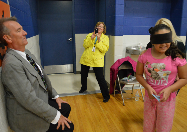 A blindfolded student doesn't know Godwin Heights Superintendent William Fetterhoff is waiting in front of the jack-o-lantern game