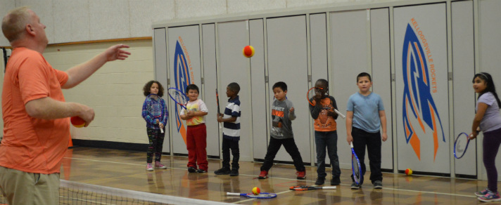 Principal Eric Schilthuis throws the ball as students take turns hitting