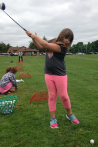 A student perfects her swing in a First Tee golf lesson