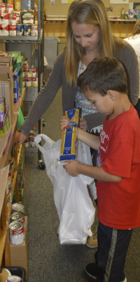 Laura Inman and her son, Micah, a Meadow Ridge student, fill a bag with weekend meals for a student