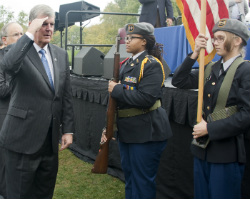 Thomas Haas, Grand Valley State University president, salutes Innovation Central High JROTC members, from left, battalion commander Chantae LaGrone and Skylar Meyer during the presentation of the colors and the pledge of allegiance