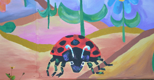 The Grouchy Ladybug character looks out at the sensory garden