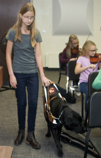 Julia enters orchestra rehearsal with her dog Duncan