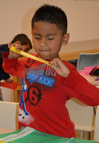 Kent City third-grader Brandon Juarez-Resendiz rips tape to connect the pieces of his design