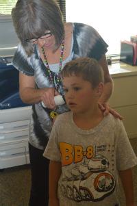 Gokey checks the temperature of first-grader Todd Lyonnais