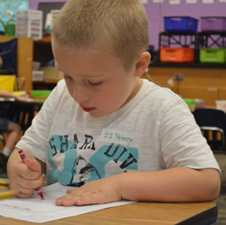 A student draws himself at kindergarten orientation