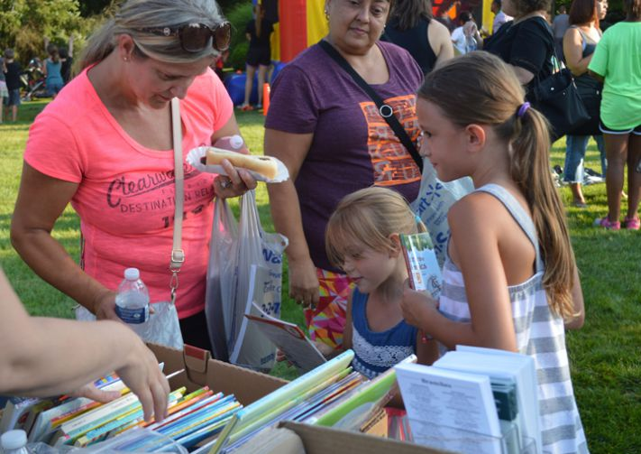 Mom Hasiba Sejdinovic helps daughters Ajla and Adelina pick out free books