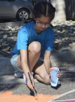 Caitlyn Chua, a junior at Comstock Park High School, quietly colors her own patch of asphalt