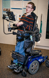 The wheelchair allows him to stand when making presentations