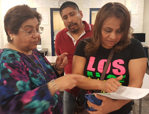 Virginia Tummelson, Kelloggsville community liaison for Hispanic families, helps Mayra Ventura and Santos Hernandez with information