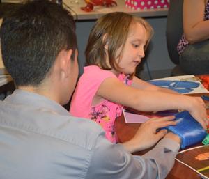 Sparta senior Dylan Avellaneda helps Baylee measure her hands