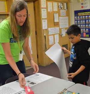 Teacher Sarah David helps a student hang up a piece of writing