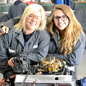 Sparta seniors and Automotive Technology students Alyssa Graham (right) and Tiffany Tasma lean on a diesel engine