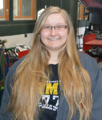 Automotive Technology student Mackenzie Olmstead in the garage where she works to replace rear shocks