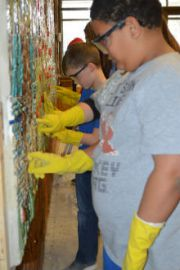 Third-grader Taychaun Donald works to clean grout from mural tiles