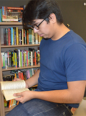 Senior Hector Zoleta reads a book from teacher Jessica Molloy's new book collection