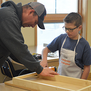 Morgan Kaiser uses a nail gun with volunteer Jason Curtis