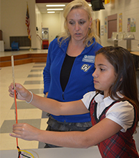 Natasha Sirrine, Grand Valley State University School of Engineering graduate student watches Melanie Delvalle construct a pipe-cleaner Eiffel Tower