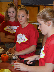 Students prepare a pepper during a Healthy High cooking class