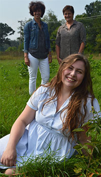 "Senior Pearl Chapman, foreground, with teachers Lynn Cvengros (left) and Dolores Keeley amid raspberry and blueberry rows on Forest Hills Eastern High land. The berries were planted through a grant from the Forest Hills Education Foundation as a ""seed"" project of the edible schoolyard"