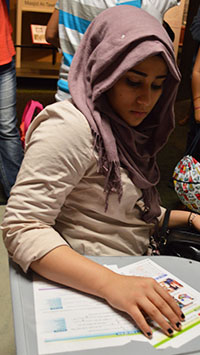 Newcomer student Zainab Ahmed sits at a school desk in the immigration exhibit