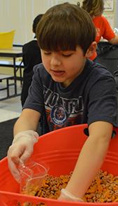 Fourth-grader Jake Agema packs trail mix for Kids Food Basket