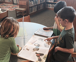 Students gather around books at an East Grand Rapids elementary school library