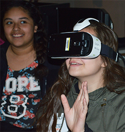 Seventh-grader Stacie Aguirre tries a virtual reality device while learning about software engineering
