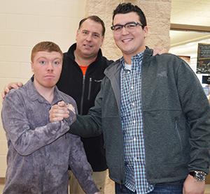 Byron Center High School senior Nick Baker, at right, greets sophomore Hunter James VandeVelde and teacher Doug Takens