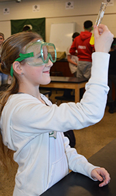 Amaris Russell examines a chemical reaction caused by mixing potassium iodide with lead nitrate