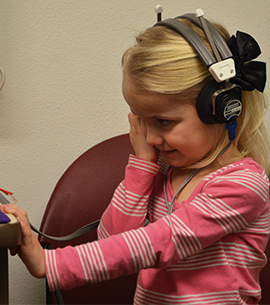 Alexis Ehling, 4, receiving a follow-up hearing screening at the Kent County Health Department