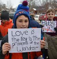 Fourth-grade student Jake Castenholz holds a sign during the march