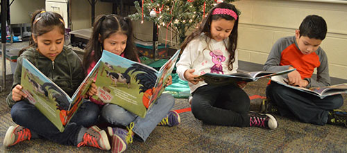 Parkview Elementary second-grade students Solymar Lopez-Argueta, Joselyn Sanchez-Rodriguez, Vanessa Matildez-Rodriguez and Juan Jimenez-Hernandez read their copies of the 2014 Michigan Reads! Book of the Year